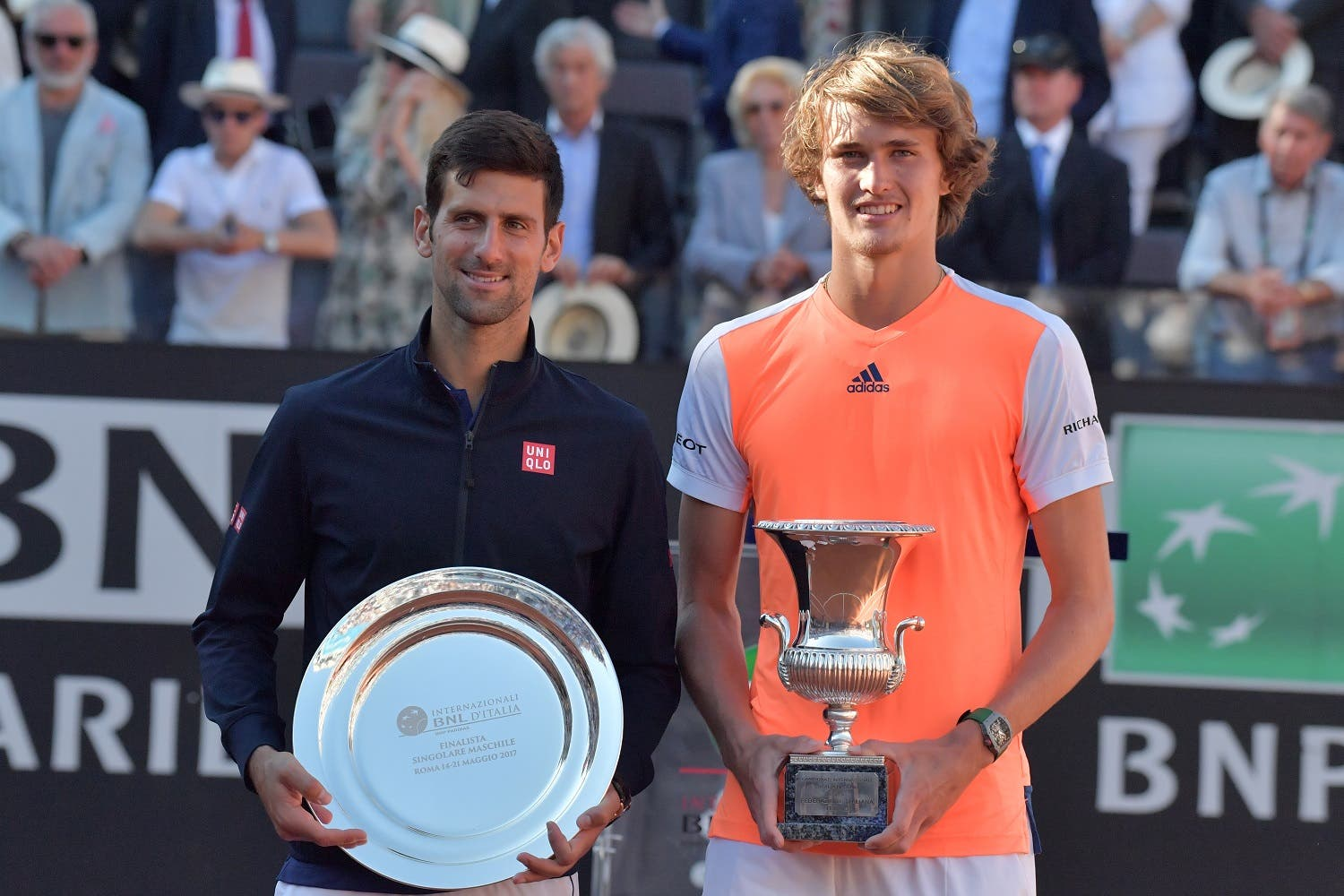 Alexander Zverev of Germany (R) poses with the trophy after winning the ATP Tennis Open final against Novak Djokovic (L) of Serbia on May 21, 2017, at the Foro Italico in Rome. Germany's Alexander Zverev stunned four-time Rome champion Novak Djokovic 6-4, 6-3 to win his first Masters title on Sunday, confirming his status as a French Open dangerman. (AFP)