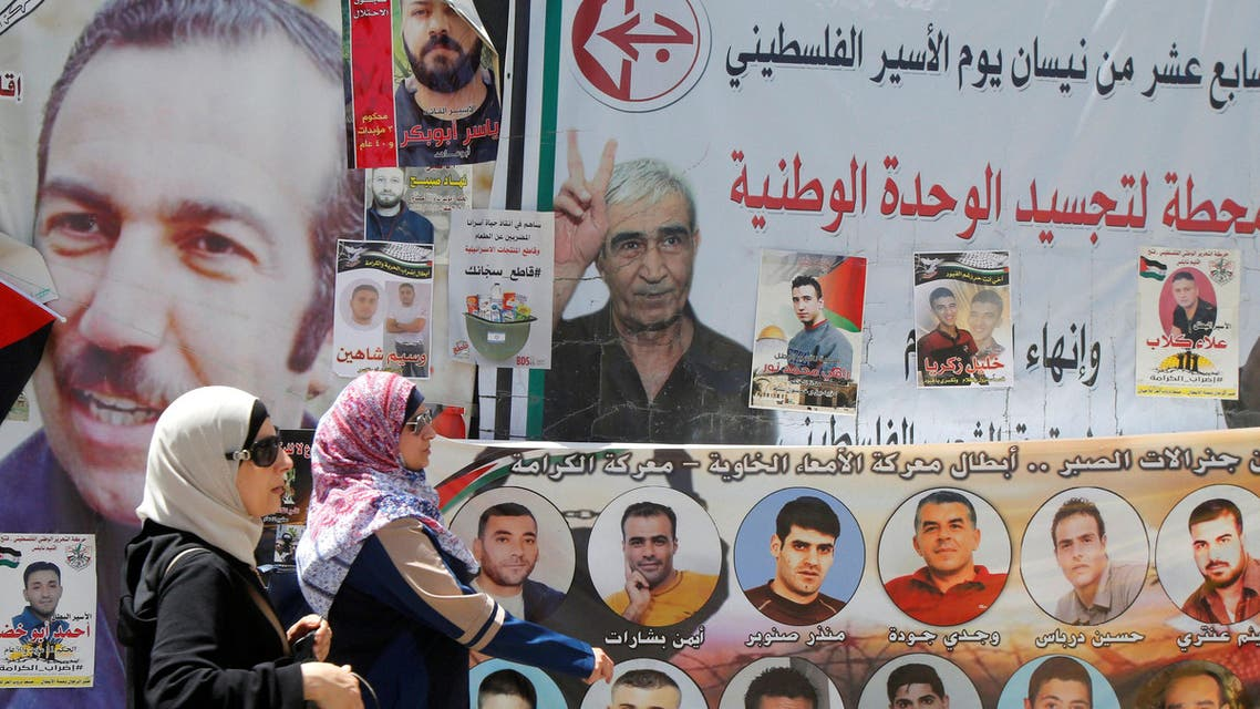 Women walk past pictures of Palestinian prisoners on hunger strike in Israeli jails, in the West Bank city of Nablus, May 9, 2017