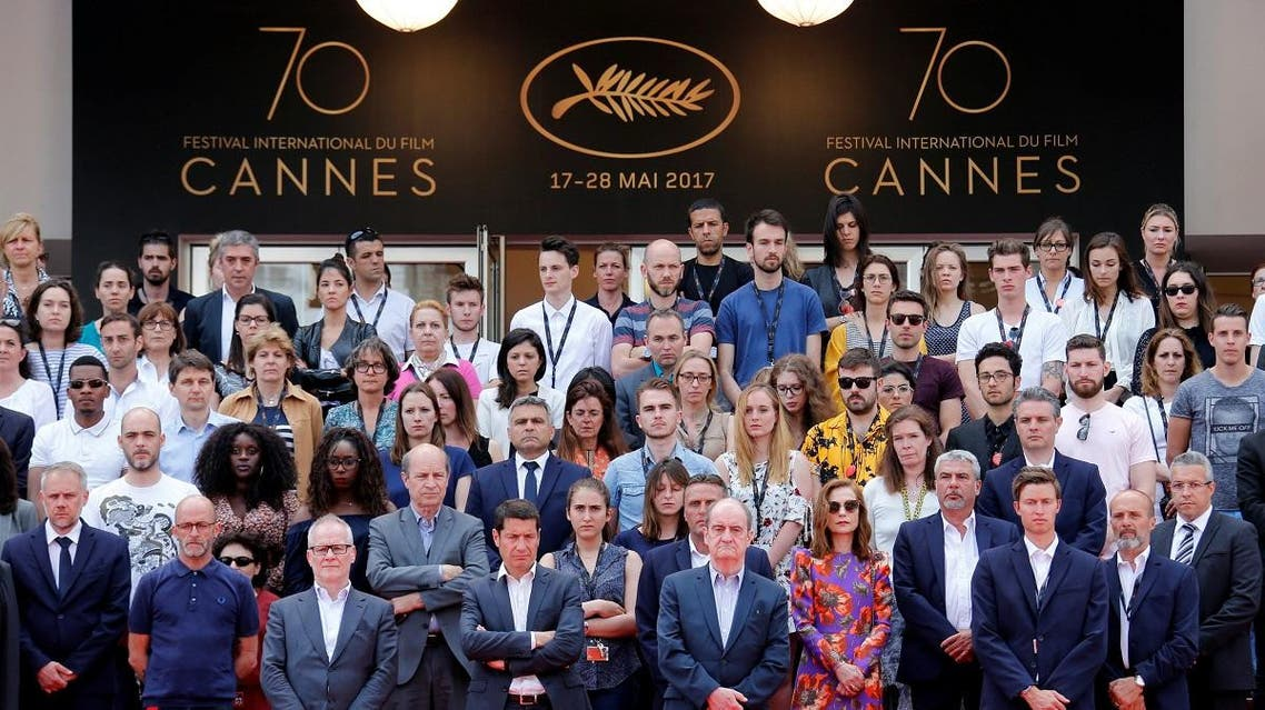 Cannes Film Festival general delegate Thierry Fremaux, Cannes Film festival president Pierre Lescure, actress Isabelle Huppert and staff members observe a minute of silence on the red carpet. (Reuters)
