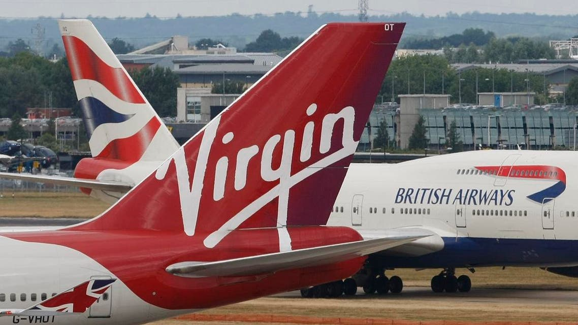 A British Airways 747 passes the tail fin of a Virgin Atlantic plane at Heathrow Airport, London. (File photo: AP)