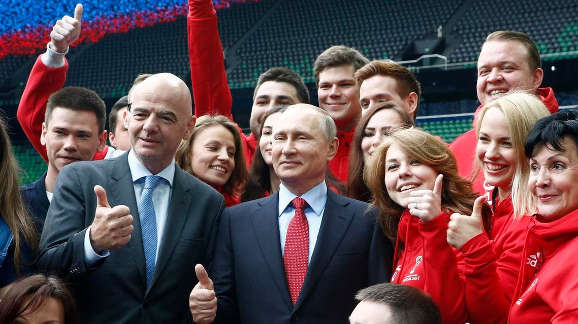 Russian President Vladimir Putin (C) and FIFA President Gianni Infantino pose for a picture with members of Russia's volunteer associations at the FC Krasnodar Stadium in the southern city of Krasnodar on May 23, 2017. (AFP)