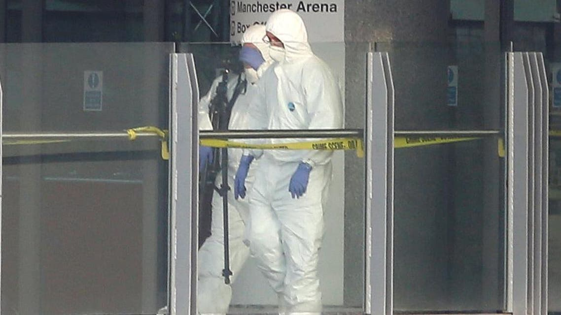 Forensics investigators work at the entrance of the Manchester Arena. (Reuters)