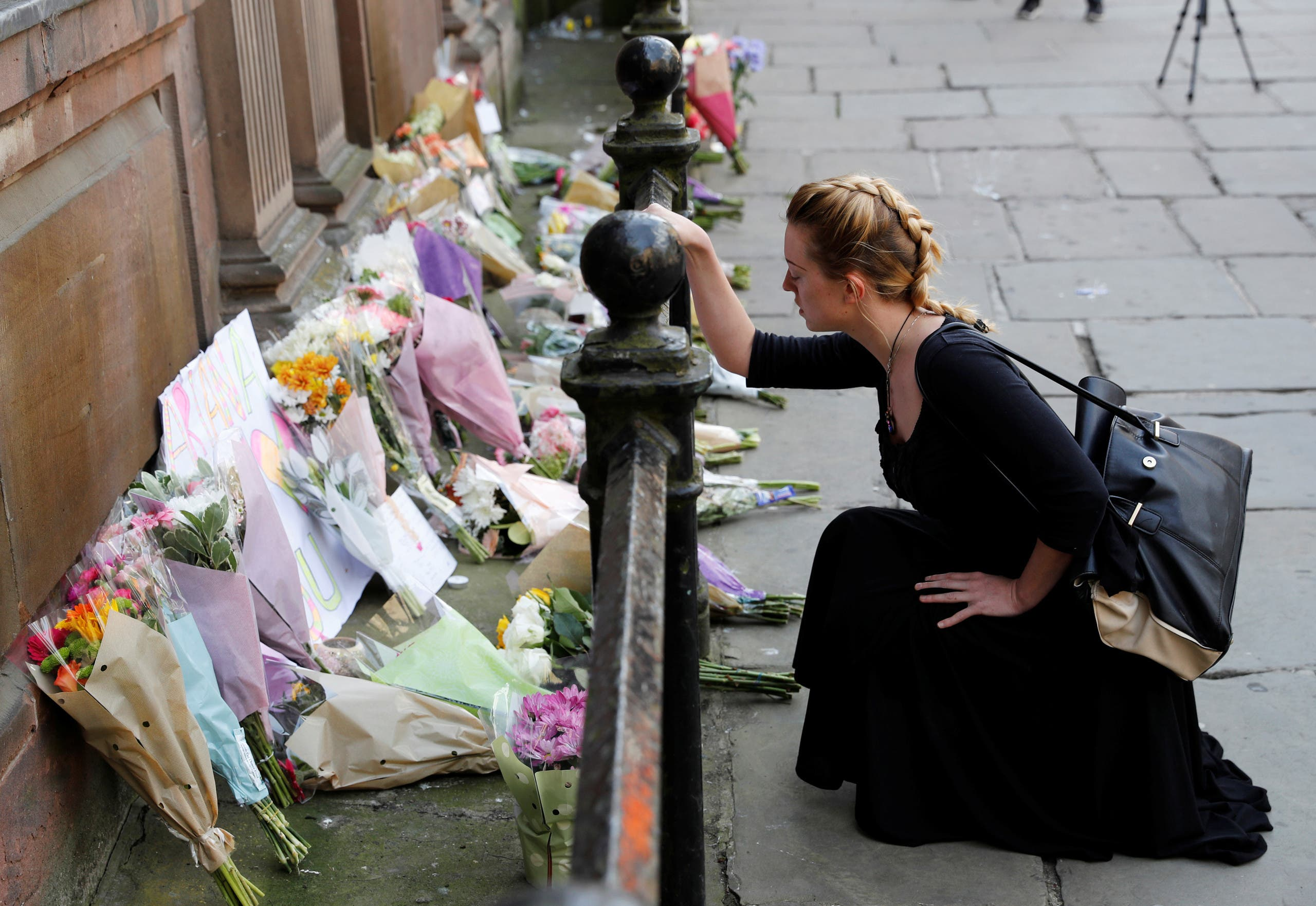 A woman lays flowers for the victims of the Manchester Arena attack, in central Manchester. (Reuters)