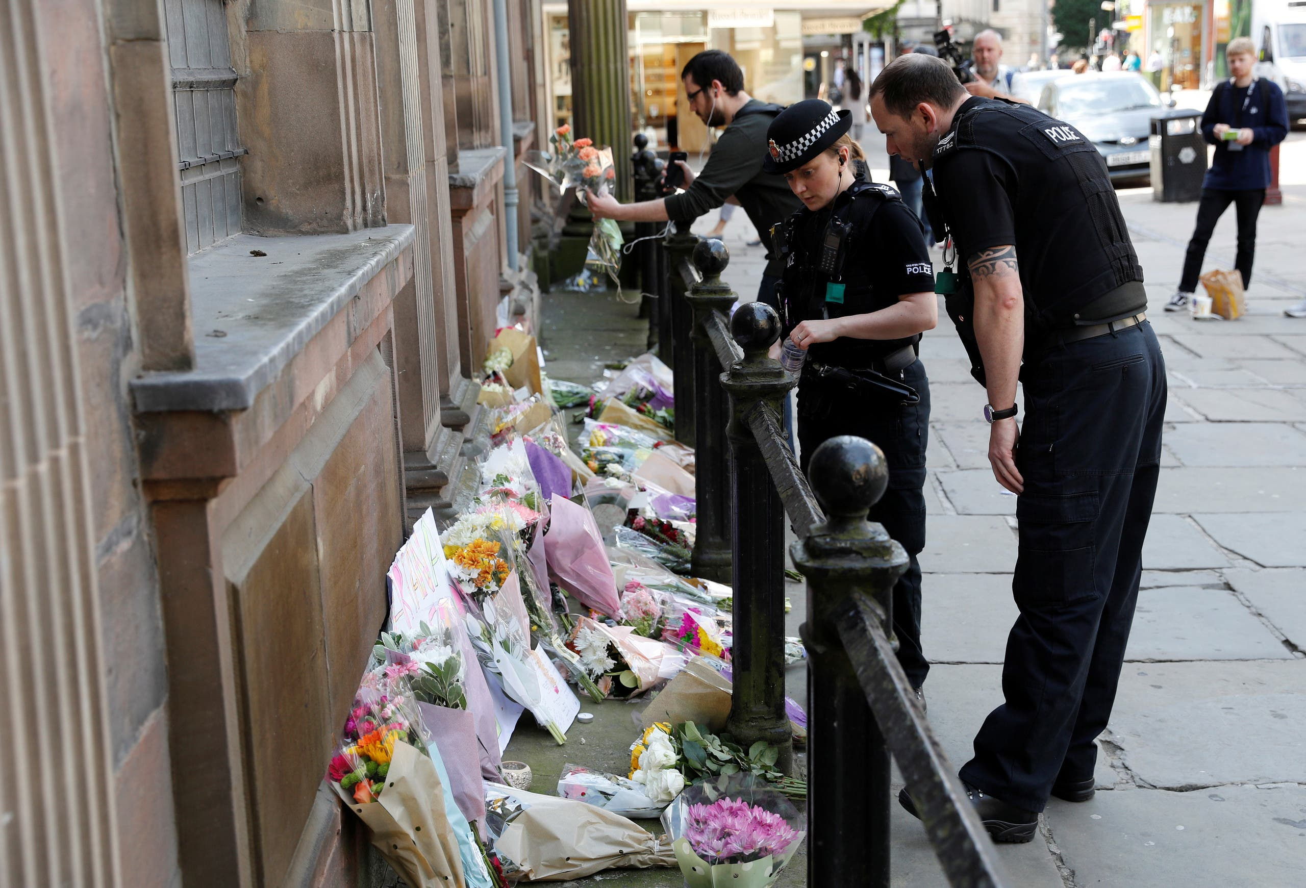 Police officers look at flowers and messages in central Manchester. (Reuters)