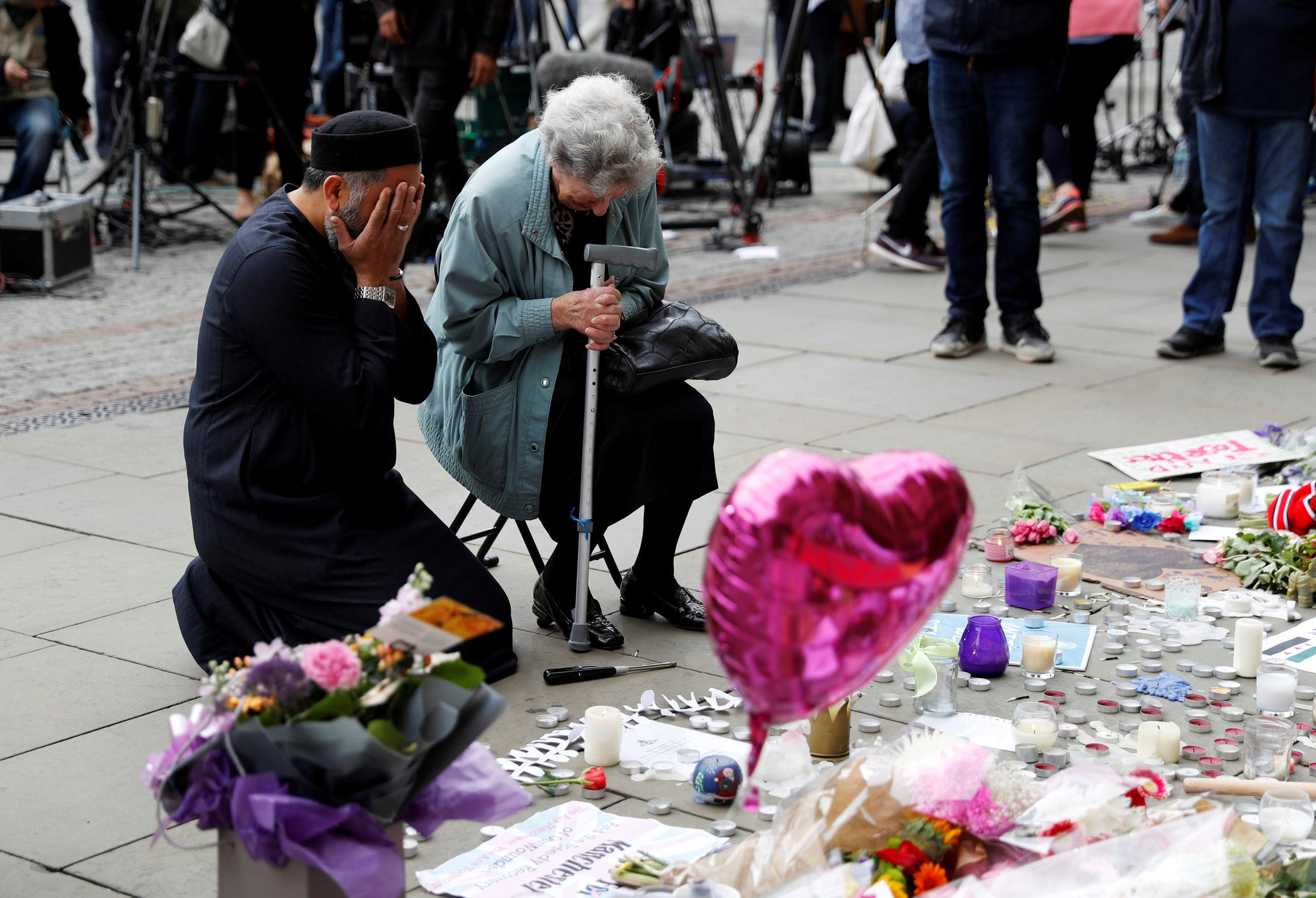 A Jewish woman named Renee Rachel Black and a Muslim man named Sadiq Patel react next to floral tributes in Albert Square in Manchester, Britain May 24, 2017. (Reuters)