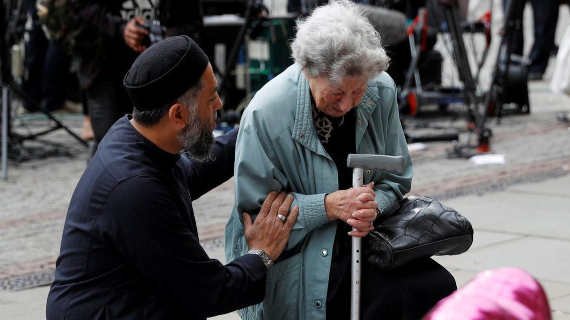 A Muslim man named Sadiq Patel comforts a Jewish woman named Renee Rachel Black next to floral tributes in Albert Square in Manchester, Britain May 24, 2017. (Reuters)