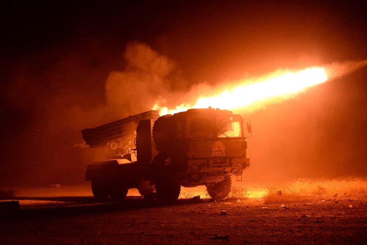 Popular Mobilization Militias fire towards ISIS militants during a battle in Qairawan, west of Mosul. (Reuters)