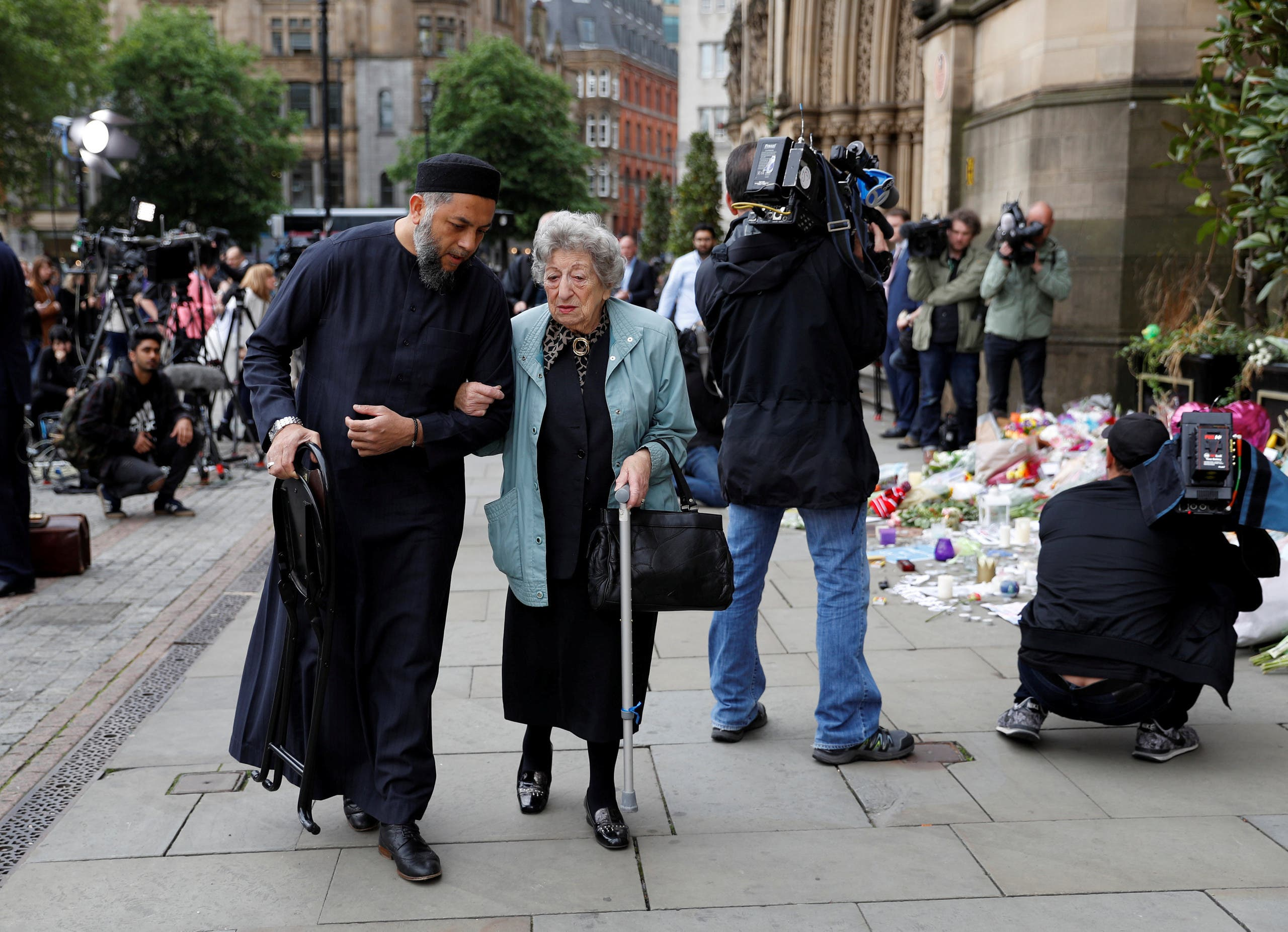 A Muslim man named Sadiq Patel and a Jewish woman named Renee Rachel Black walk by floral tributes in Albert Square in Manchester, Britain May 24, 2017. (Reuters)