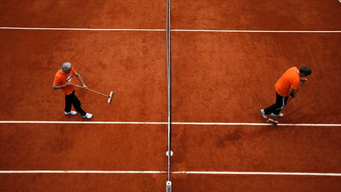 Workers clean the court during a men's singles match between Ernests Gulbis of Latvia and Facundo Bagnis of Argentina at the French Open tennis tournament at the Roland Garros stadium in Paris. (Reuters)