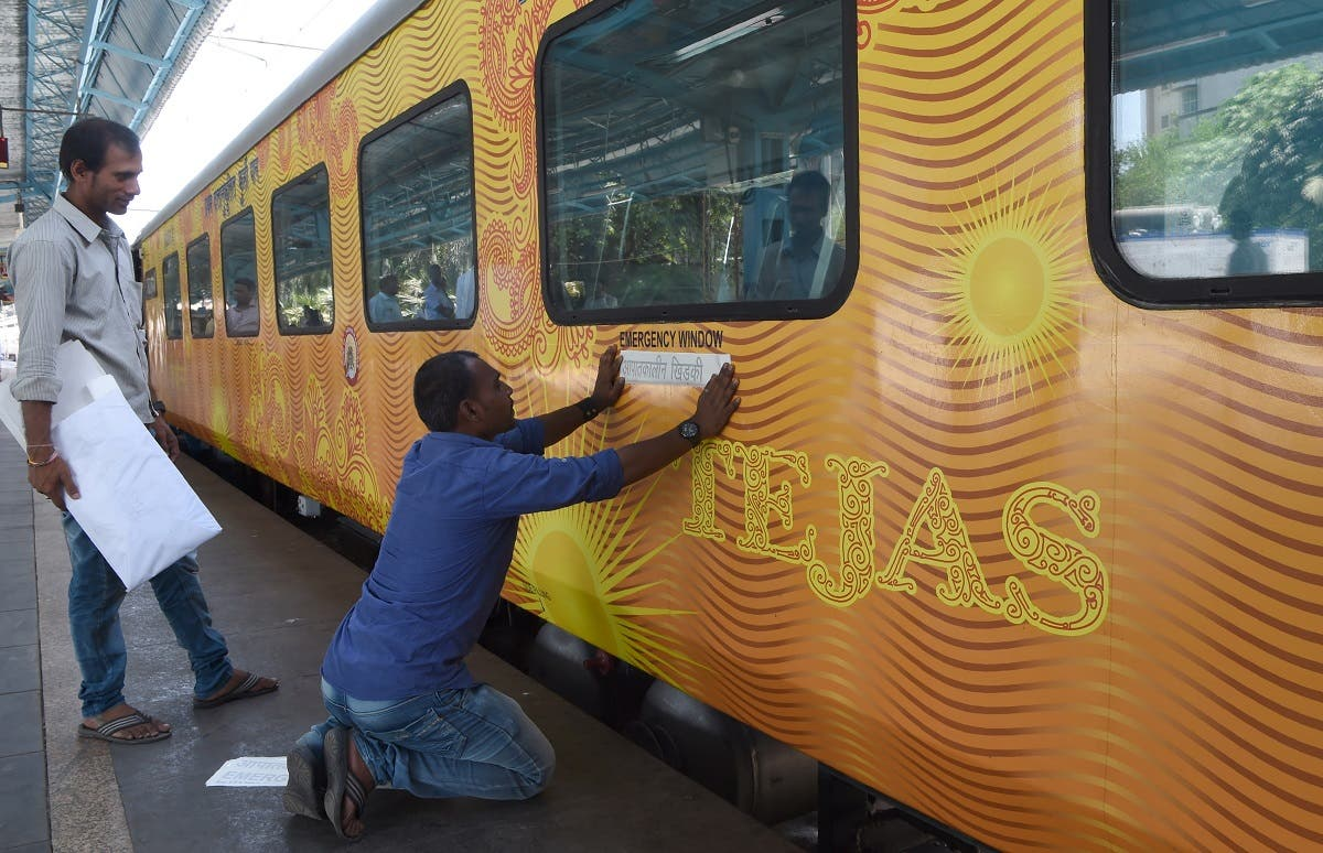 In this photograph taken on May 21, 2017, Indian staff paste stickers below an emergency window of the Tejas Express luxury train before its first journey between Mumbai and Goa. (AFP)