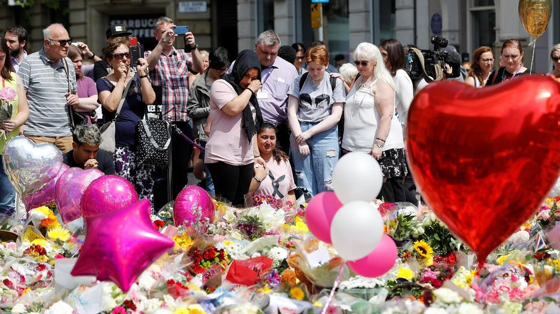 People react as they look at floral tributes for the victims of the Manchester Arena attack,in St Ann's Square, in central Manchester, Britain May 25, 2017. (Reuters)