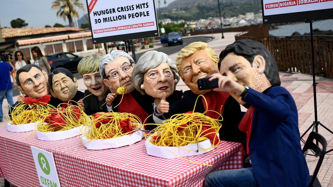 نشطاء يرتدون أقنعة قادة مجموعة الدول الصناعية السبع الكبرى