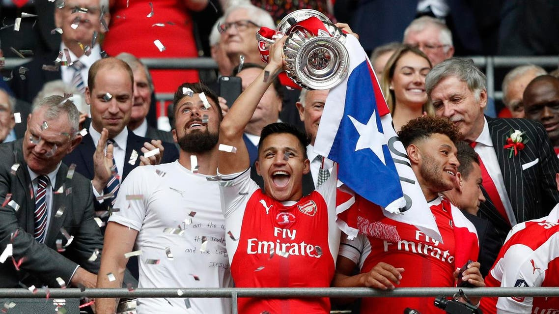 Arsenal's Chilean striker Alexis Sanchez lifts the FA Cup trophy as Arsenal players celebrate their victory over Chelsea in the English FA Cup final football match between Arsenal and Chelsea at Wembley stadium in London on May 27, 2017. (AFP)