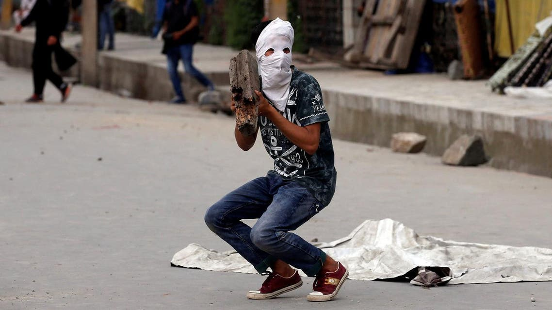 A masked protester prepares to throw a rock towards the Indian police during a protest after Friday prayers, in Srinagar, May 26, 2017. (Reuters)