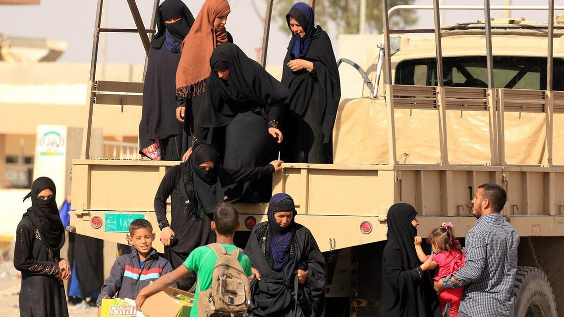 Displaced Iraqis get out of a military truck as they wait for transfer to displacement camps south of Mosul, Iraq, on May 23, 2017. (Reuters)