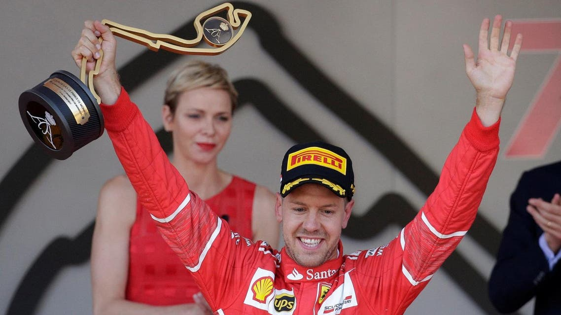 Ferrari's Sebastian Vettel celebrates winning the race on the podium with the trophyReuters