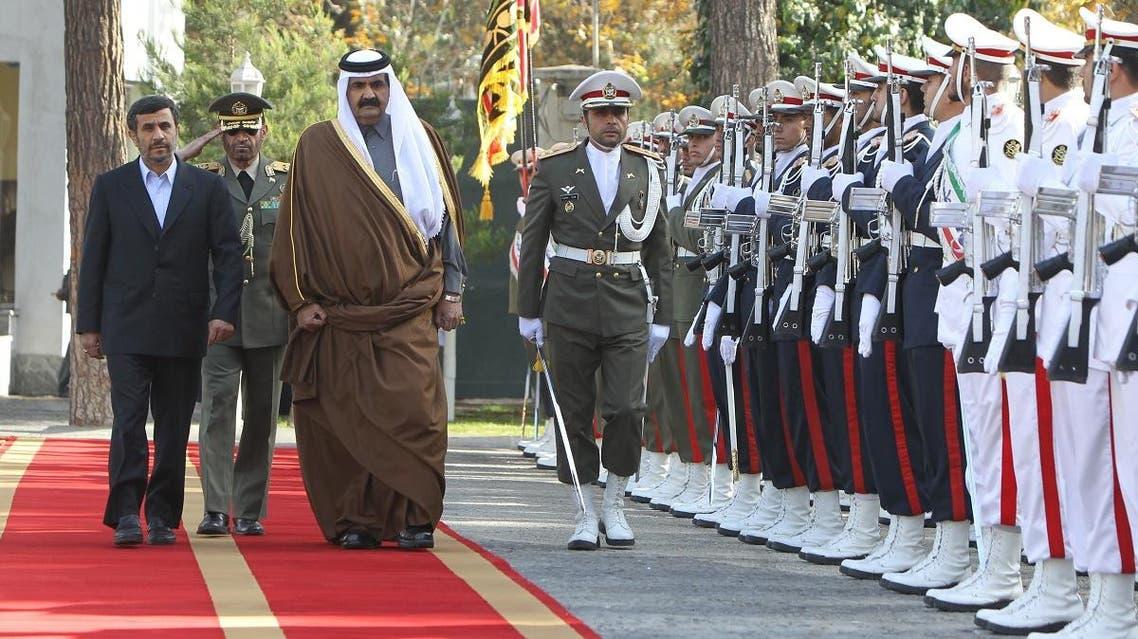 Former Iranian President Mahmoud Ahmadinejad (L) and Former Qatari Emir Sheikh Hamad Bin Khalifa al-Thani inspect the honor guard during a welcoming ceremony prior to their meeting in Tehran in 2010. (AFP)