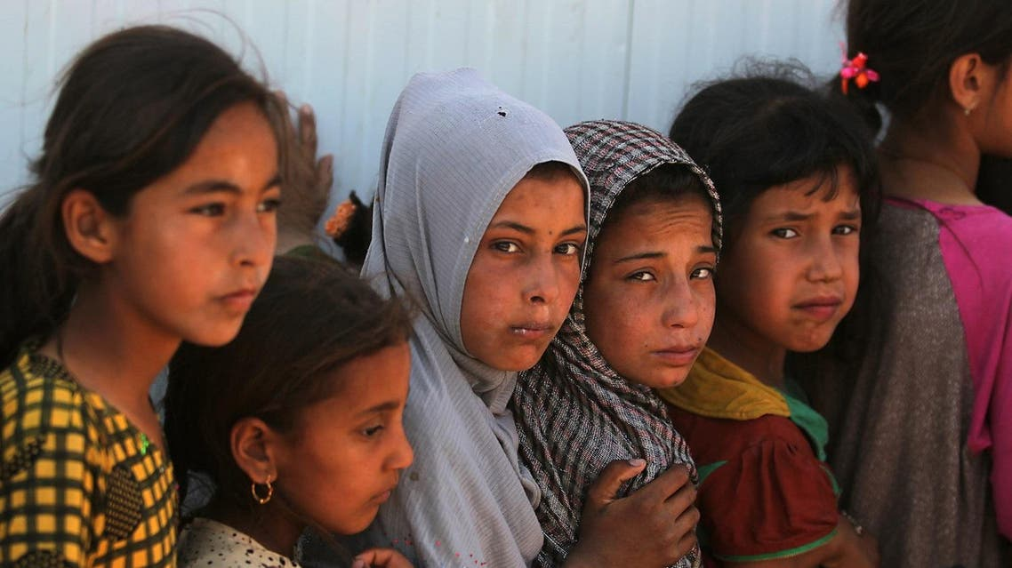 Displaced children stand in line to get food at the Hammam al-Alil camp for internally displaced people south of Mosul, on May 25, 2017, as government forces continue their offensive to retake the city of Mosul from Islamic State (IS) group fighters. (AFP)