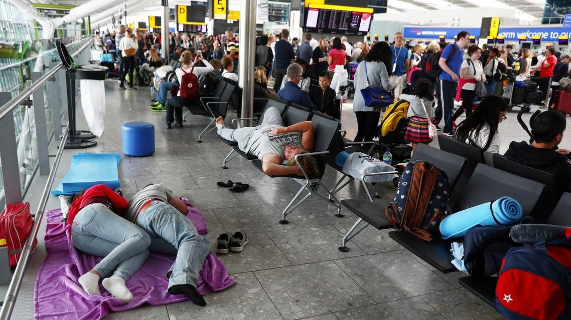 People sleep next to their luggage at Heathrow Terminal 5 in London. (Reuters)