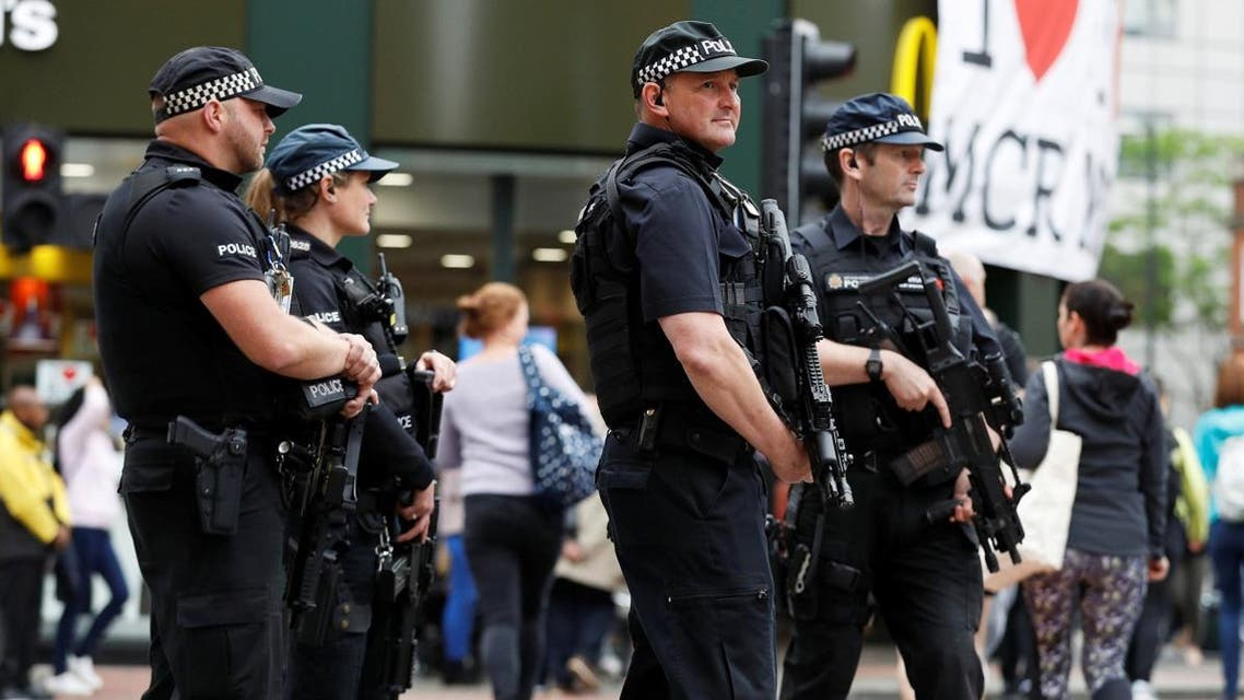 Armed police officers stand on duty in central Manchester. (Reuters)