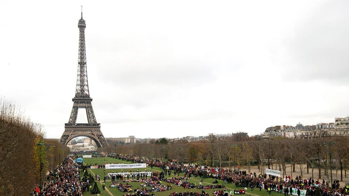 "(FILES) This file photo taken on December 12, 2015 shows Several Non Governmental Organisations (NGO)as they gather to form a human chain reading ""+3°C SOS"" on the Champs de Mars near the Eiffel Tower in Paris on the sidelines of the COP21, the UN conference on global warming. Donald Trump has decided to pull the United States out of the Paris climate accord, US media reported May 31, 2017, as the president kept the world guessing -- saying an announcement will come in the ""next few days.""An American pullout would deal a devastating blow to global efforts to combat climate change less than 18 months after the historic 196-nation pact was signed in Paris, fruit of a hard-fought agreement between Beijing and Washington under Barack Obama's leadership. (AFP)"