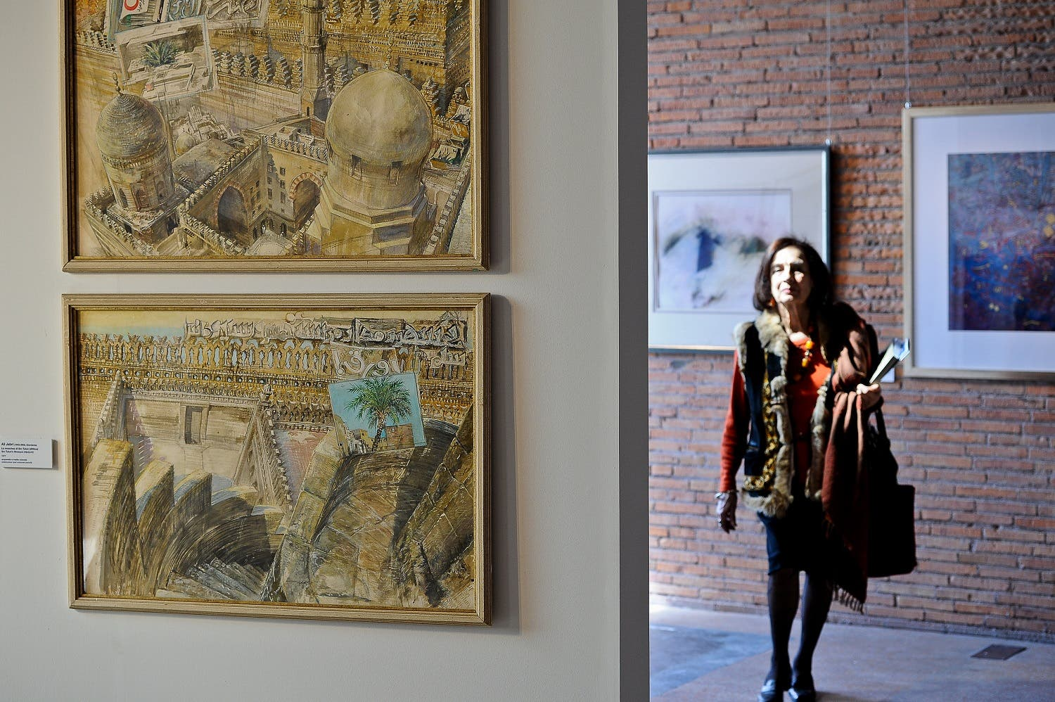 "A visitor walks during the exhibition ""Reflections from heaven, meditations on earth: modern calligraphic art from the Arab world"" at the Mercati di Traiano in Rome on March 21, 2012. (AFP)"