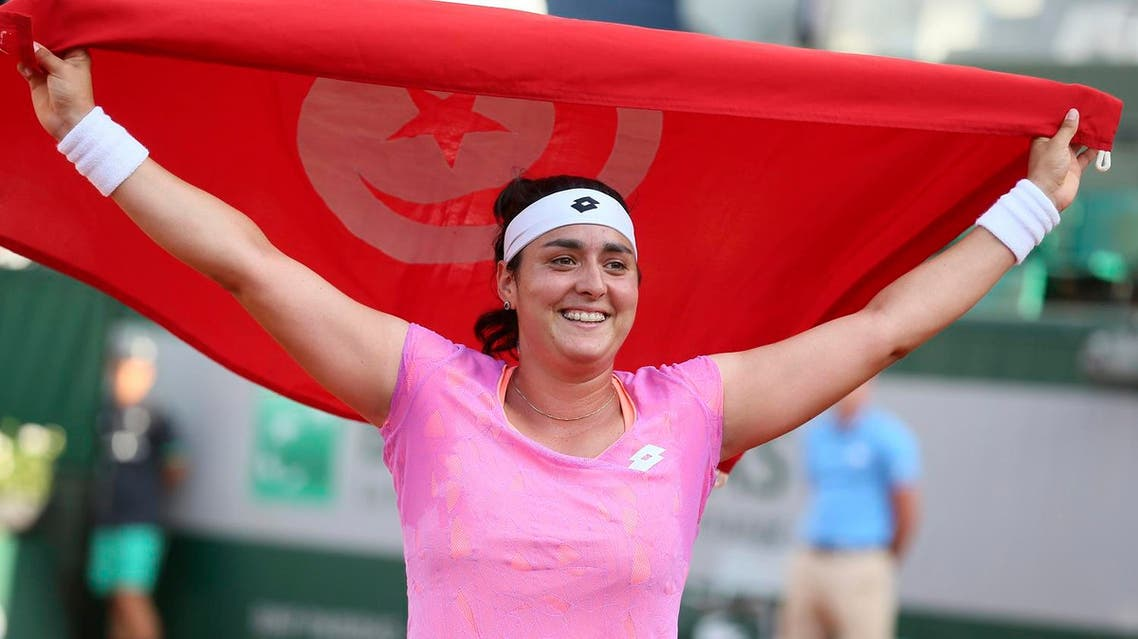 Ons Jabeur holds up Tunisian flag after winning against Slovakia's Dominika Cibulkova at the Roland Garros 2017 on May 31, 2017. (AFP)