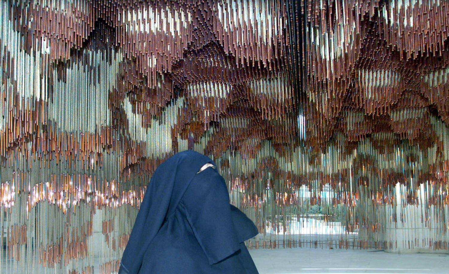 "A woman looks at a rope and cooper life-size reproduction of the ceiling of the Palatine Chapel in Palermo (sec XII, designed by Muslim craftsmen for King Ruggero II, at ""Islam in Sicily"" exhibition on July 11, 2002. (Reuters)"