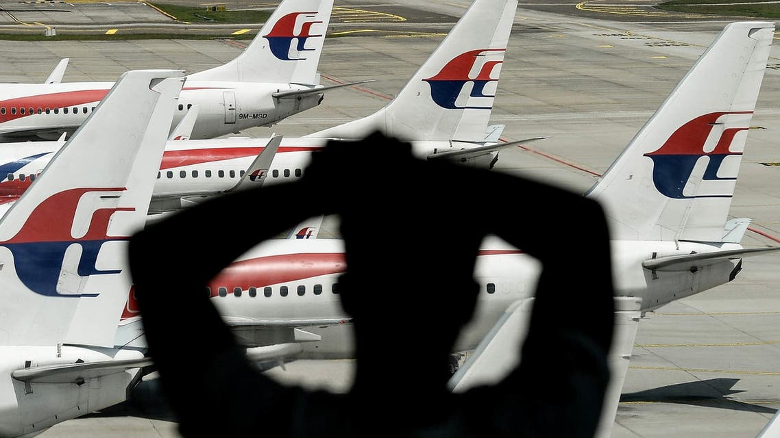A man looks at Malaysia Airlines' aircraft parked on the tarmac at Kuala Lumpur International Airport in Sepang on February 25, 2016. AFP