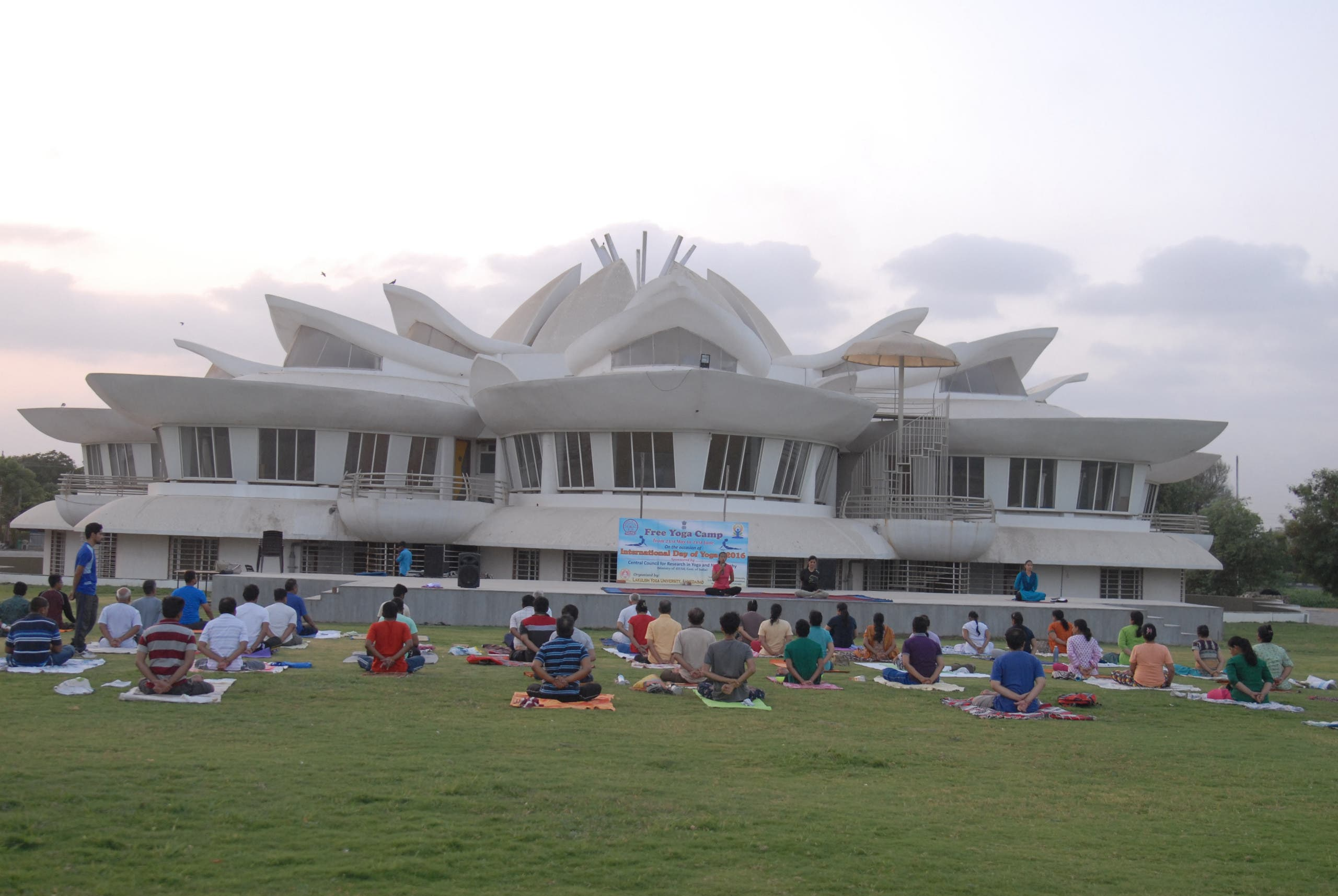 A unique lotus-shaped building with many people doing yoga on open ground. (Supplied)