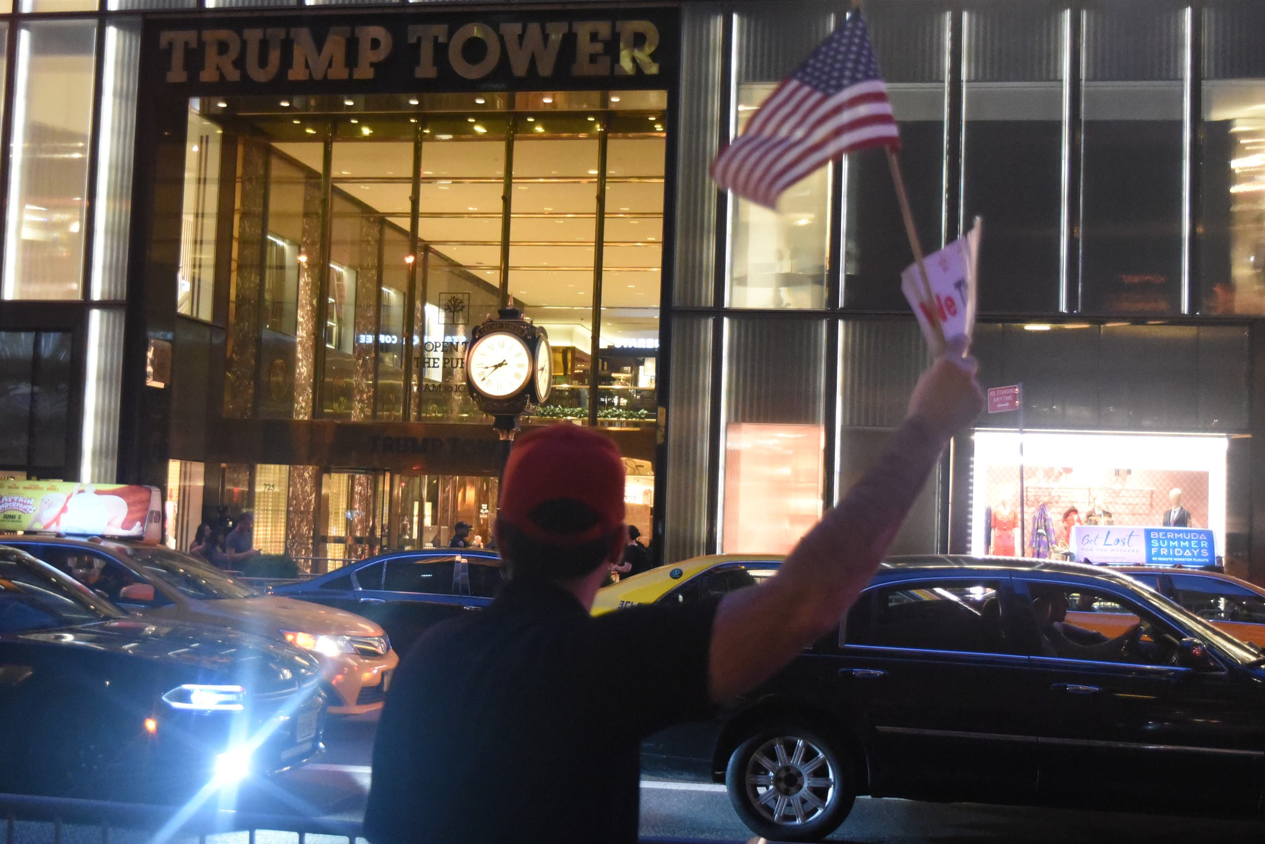 Trump2: A pro-Trump counter-protestor holds the American flag in front of Trump Tower.