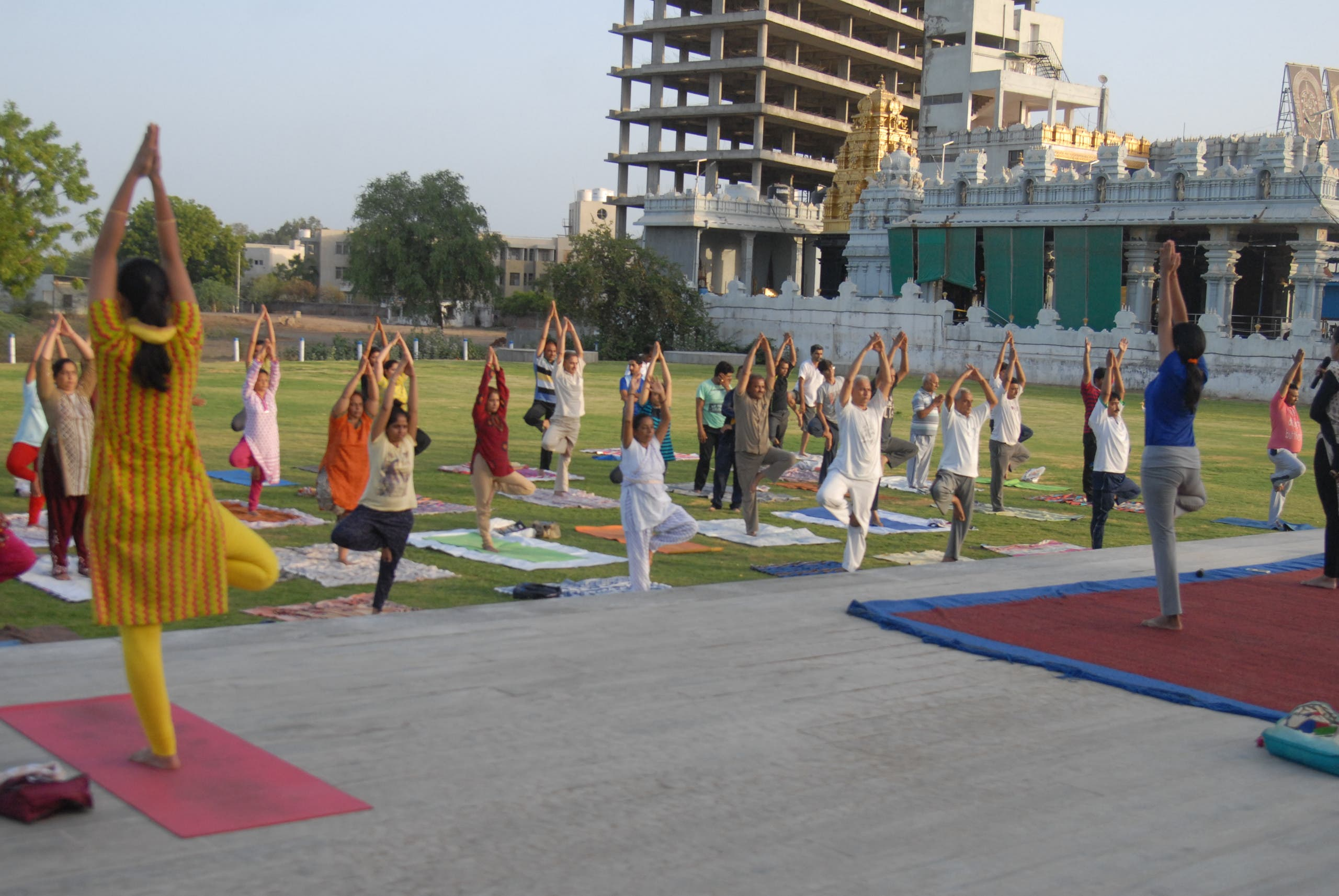 Woman instructors leading yoga exercises with a group of people. (Supplied)