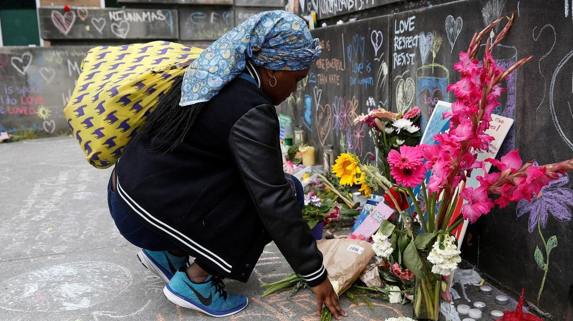 Muslim woman, who preferred not to giver her name, prays at a makeshift memorial. (Reuters)