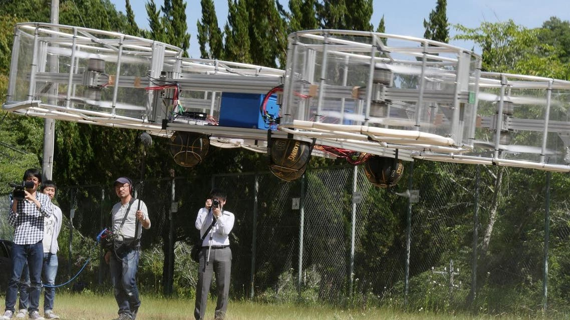 Journalists film Cartivator's flying car during its demonstration in Toyota. (Reuters)