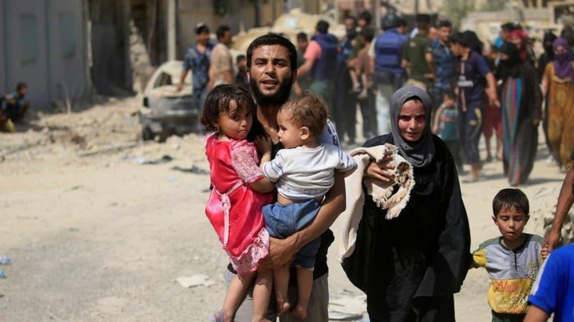 نازح عراقي فر من اشتباكات يحمل طفلين في غرب الموصل يوم السبت