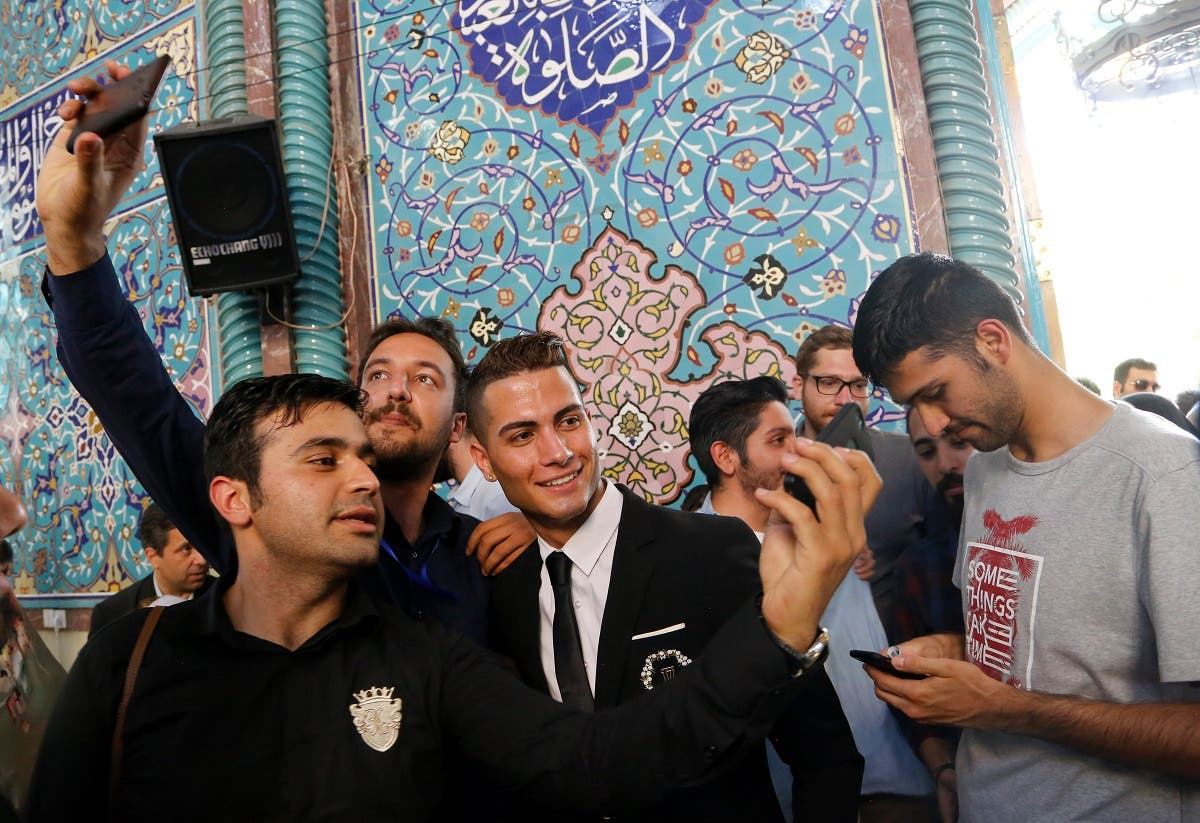 Iranians take selfies with Iranian Reza Alireza Lou (C), a look-alike of Real Madrid's Portuguese soccer super star Cristiano Ronaldo, during the Iranian presidential elections at a polling station in Tehran on May 19, 2017.  (STR/AFP)