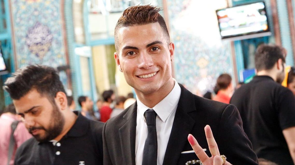 Iranian Reza Alireza Lou, a look-alike of Real Madrid's Portuguese soccer player Cristiano Ronaldo, holds his ID card as he poses for photographs during the Iranian presidential elections on May 19, 2017 at a polling station in Tehran.  (STR/AFP)