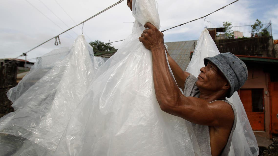 Filipino worker Dario Llaguno gathers used plastic sheets which were dried out in the sun at a junk shop in suburban Caloocan, north of Manila, Philippines on Wednesday, Sept. 12, 2012. (AP)