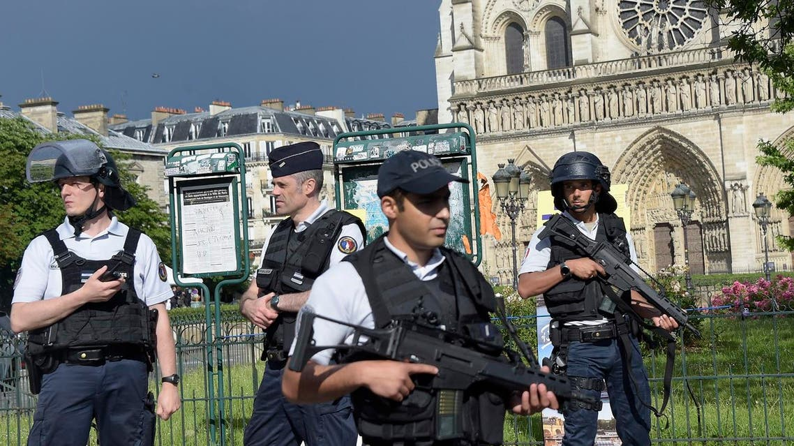 French police officials gather at the site of an attack near the entrance of Notre-Dame cathedral in Paris on June 6, 2017. Anti-terrorist prosecutors have opened a probe after police shot and injured a man who had tried to attack an officer with a hammer outside Notre Dame cathedral. The officer was slightly injured in the attack outside the world-famous landmark in central Paris. One of his colleagues responded by shooting him, wounding the attacker, whose motives were not immediately known, according to a police source. (AFP)