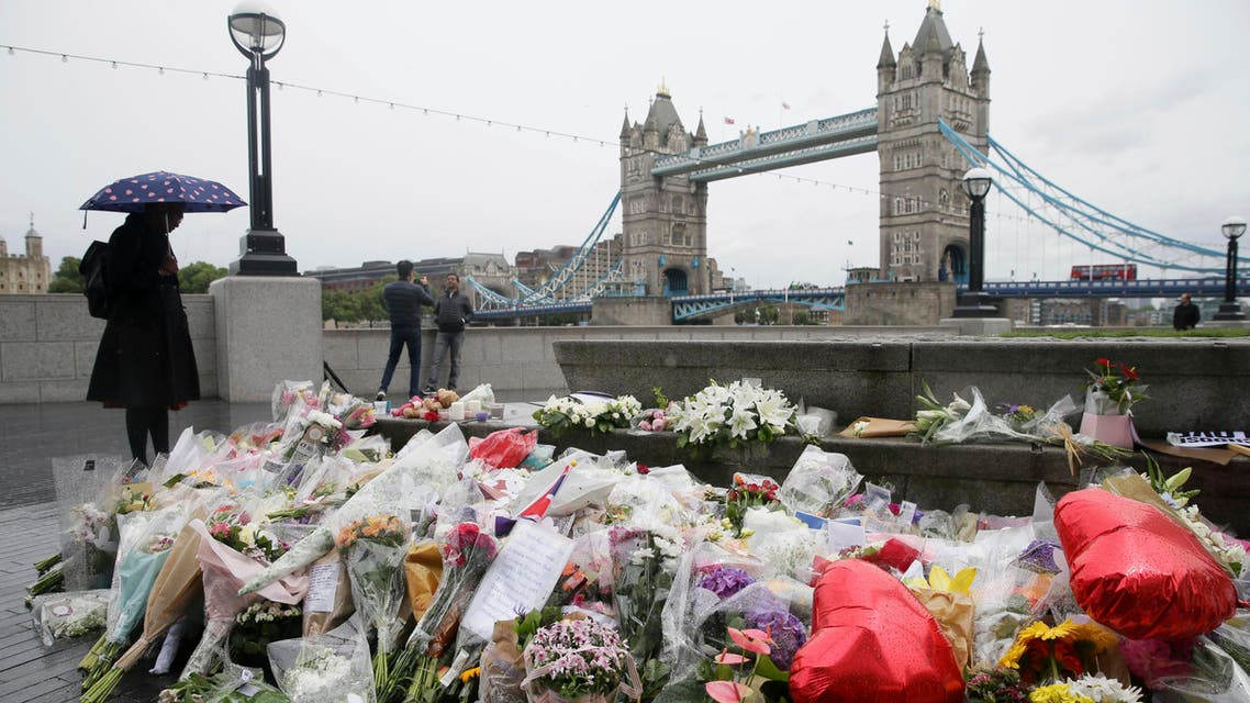 A woman at looks at flowers placed for attack victims at Potters Field Park in London, Tuesday, June 6, 2017. AP