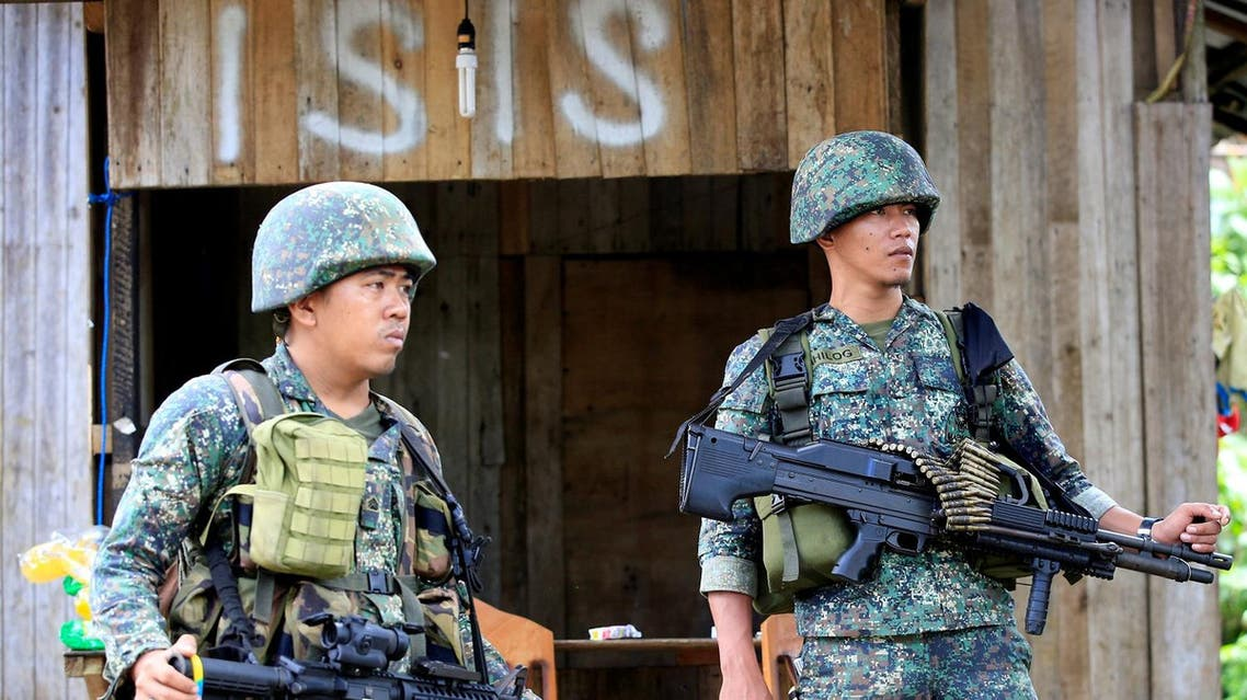 Soldiers stand guard along the main street of Mapandi village as government troops continue their assault on insurgents from the Maute group, who took over large parts of Marawi City, Philippines. (Reuters)