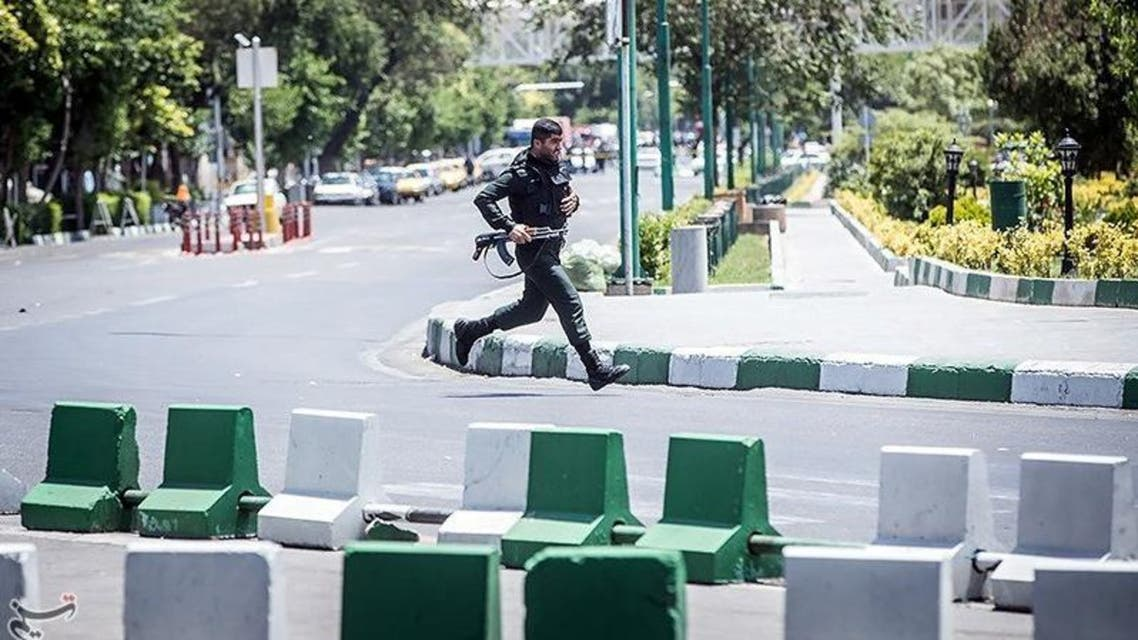 A member of Iranian forces runs during an attack on the Iranian parliament in central Tehran, Iran, June 7, 2017