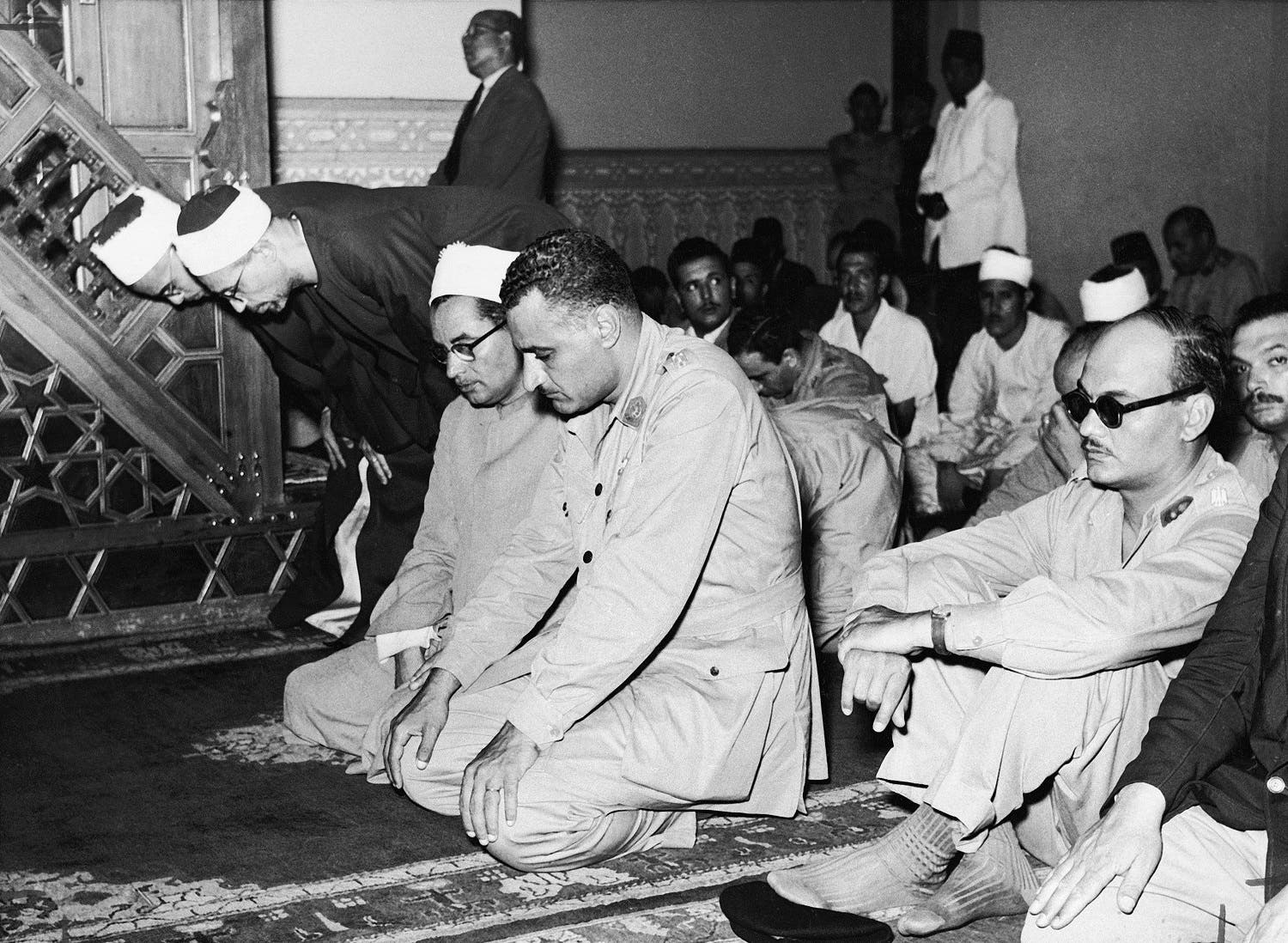 Egyptian Prime Minister Lt. Col. Gamal Abdel Nasser prays at a Cairo mosque with the Minister of National Guidance, Maj. Salah Salem, right, in sunglasses, in 1954. (AP)
