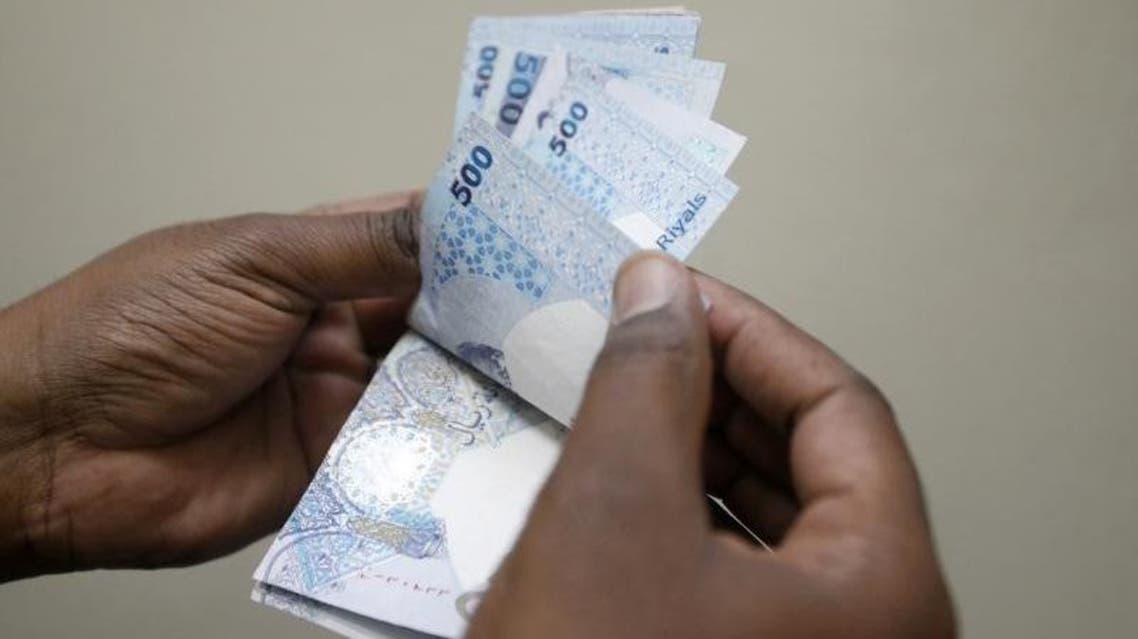 Reuters photo of a man who makes banknotes from the Qatari riyal. reuters