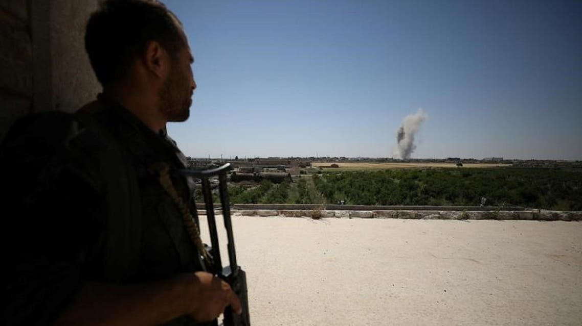 A Syrian Democratic Forces fighter watches smoke billowing from al-Mashlaab district in Raqqa. (Reuters)