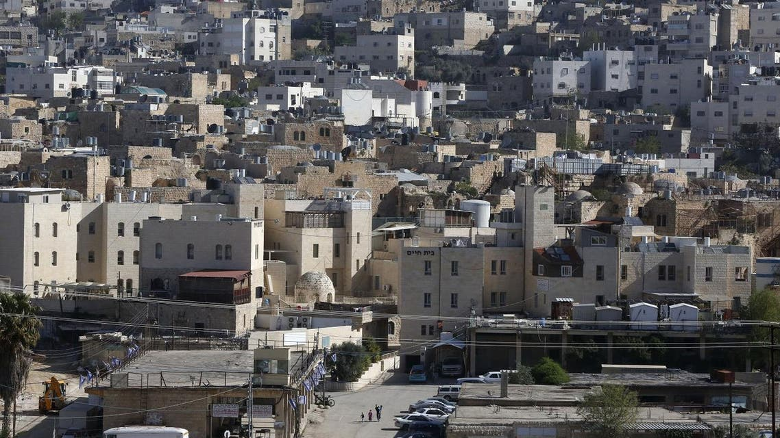 A picture taken on April 6, 2017 shows a general view of the Israeli settlement of Abraham Avino (back) in the centre of the Old City of the Palestinian city of Hebron (bottom) in the occupied West Bank. AFP