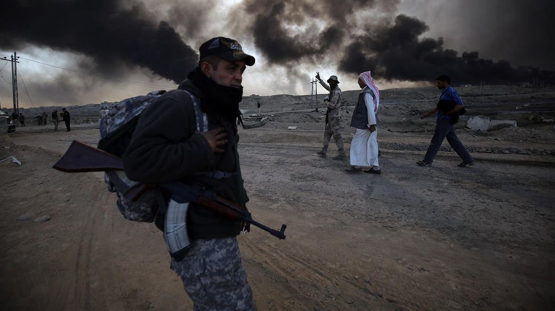 """A Sunni fighter from the Popular Mobilization Forces stands guard in an area east of Mosul, as displaced Iraqi families flea areas of unrest, on October 22, 2016, during an operation to retake the main hub city from the Islamic State (IS) group jihadists. Mosul is the most populous city in the """"caliphate"""" Baghdadi declared in June 2014, and the operation to recapture it is Iraq's largest in years. AFP"""