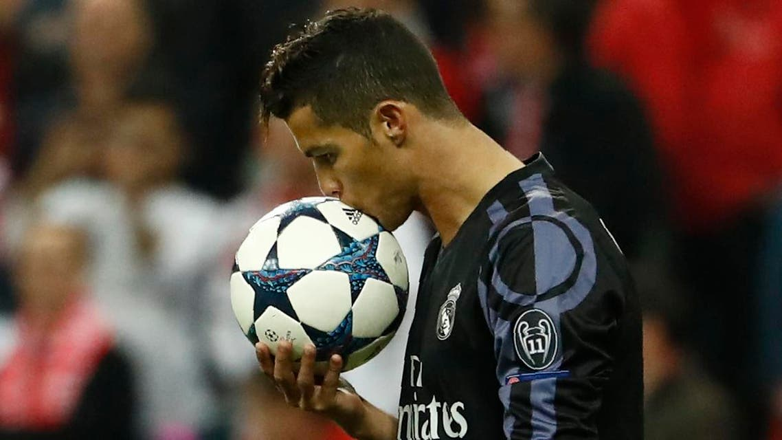 (FILES) This file photo taken on April 12, 2017 shows Real Madrid's Portuguese forward Cristiano Ronaldo kissing the ball before taking a free kick during the UEFA Champions League 1st leg quarter-final football match FC Bayern Munich v Real Madrid in Munich, southen Germany. State prosecutors have filed a complaint on June 13, 2017 against the Portuguese star, who they accuse of taking advantage of a corporate structure to defraud the Spanish Treasury of 14.7 million euros. (AFP)