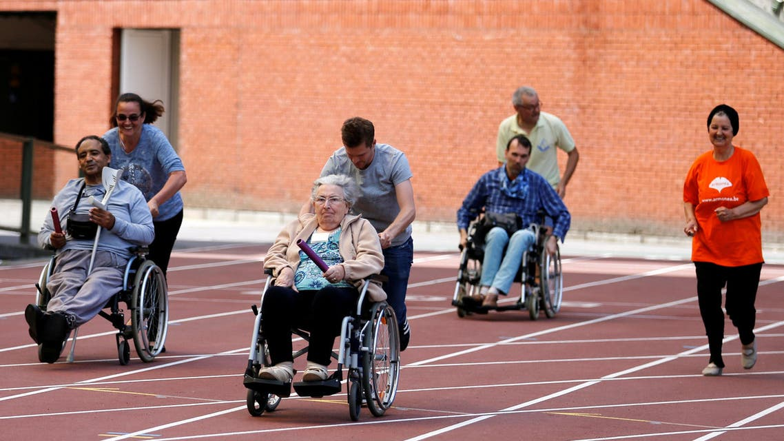 "A participant is pushed by an assistant as they take part in the 4x25 metres relay during the ""Olympics for Seniors"" event at King Baudouin stadium in Brussels, Belgium June 13, 2017"