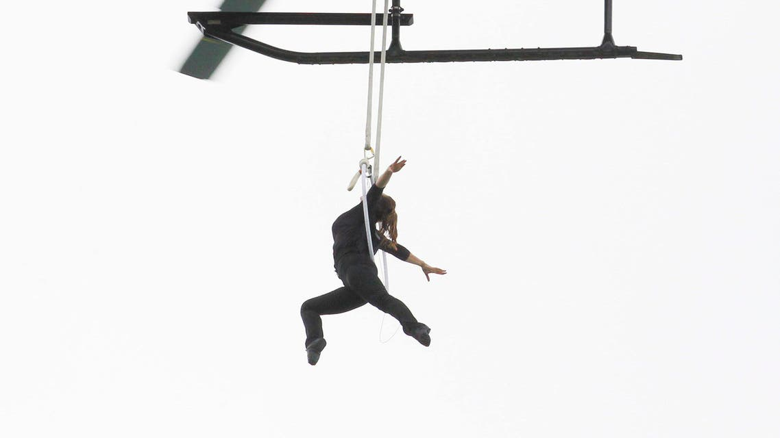 Nik Wallenda watches from above as his wife, Erendira Wallenda, hangs by her teeth while suspended from a helicopter above Niagara Falls in Niagara Falls, N.Y., Thursday, June 15, 2017. (AP)